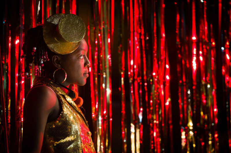 Girl stands in front of red glitter curtain