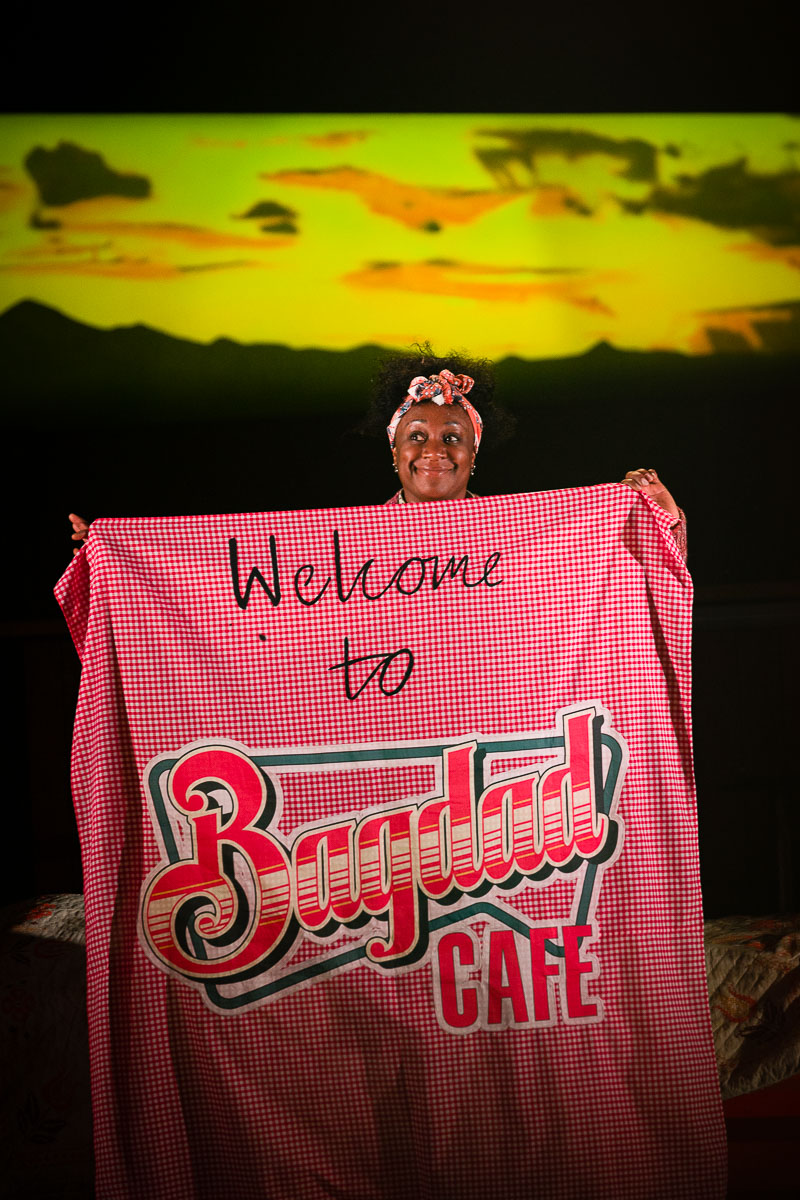 Woman holds sign saying Welcome to Bagdad Cafe