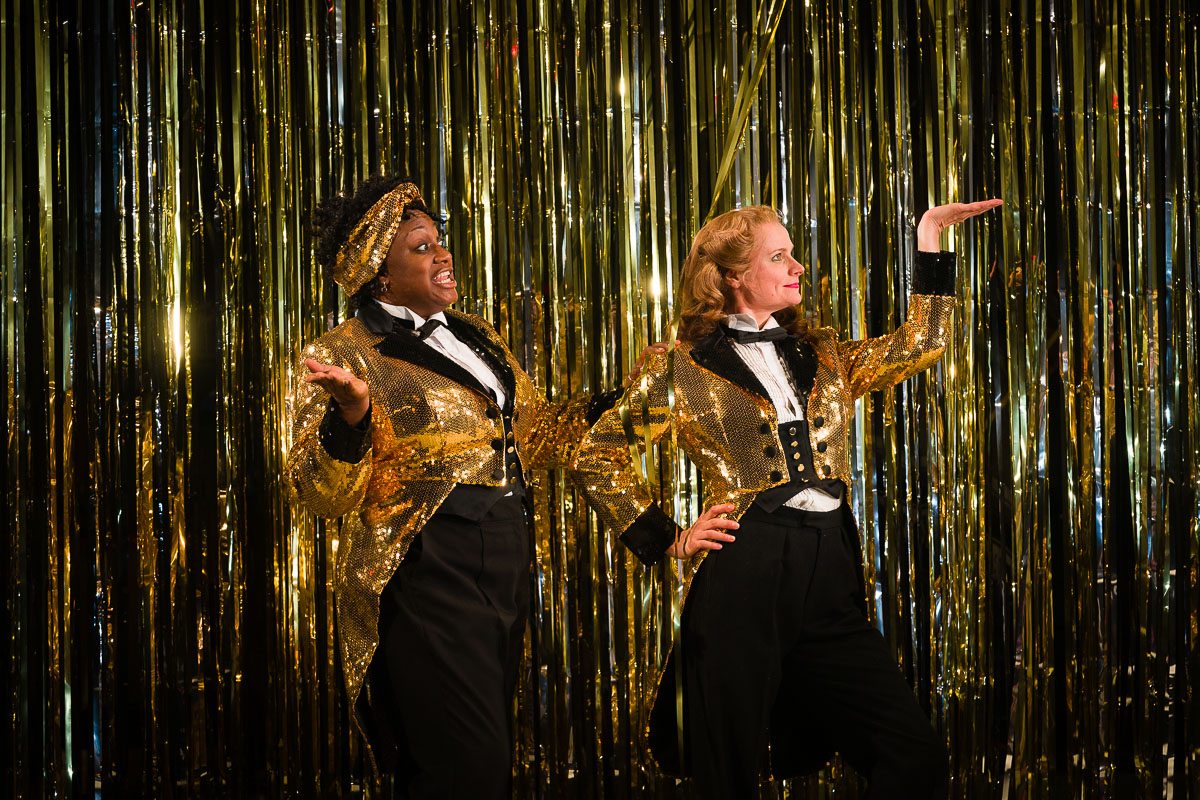 Two women dance in gold sparkly jackets